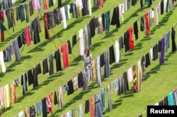 """A woman walks among dresses and skirts hanging inside a stadium, in an art exhibition titled """"Thinking of You"""" by Kosovo-born, London-based artist Alketa Xhafa-Mripa, in Pristina, June 12, 2015. Dresses and skirts donated by Cherie Blair and Rita Ora were among 5,000 pegged to clotheslines in the Kosovo stadium in an exhibit aimed at drawing attention to the stigma suffered by victims of wartime sexual violence."""