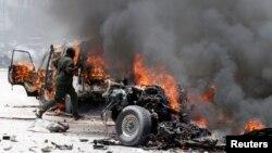 Polisi Somalia berlari ke lokasi bom mobil yang meledak dekat istana Presiden di Mogadishu, Somalia, Senin (18/3).