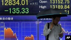 A man checks his mobile phone in front of the electronic stock board of a securities firm in Tokyo, June 2013.