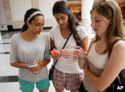 FILE - Isabella Cimato, left, Arianna Schaden and Sofia Harrison check their phones at Roosevelt Field shopping mall in Garden City, N.Y.