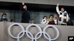 Thomas Bach, prezidan Komite Entènasyonal Olenpik la, ak Prezidan Kore di Sid la, Moon Jae-in, ki t ap salye piblik la pandan seremoni fèmti Je Zolenpkik d Ivè 2018 yo nan Pyeongchang, nan Kore di Sid. (Foto: 25 fevriye 2018).