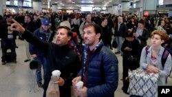 Los pasajeros miran hacia arriba a un tablero del horario del tren mientras que esperan en la estación de Penn de Nueva York, lunes, 3 de abril, 2017.