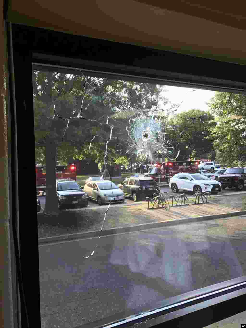 Emergency personnel are seen through a window with a bullet hole in Alexandria, June 14, 2017.