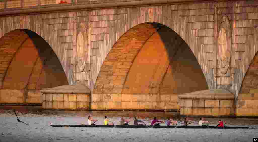 A rowing team passes the Memorial Bridge during practice on the Potomac River early in the morning in Washington.