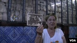 Thylda Lellouche holds a photo of her Tunisian grandfather and uncle while visiting the Ghriba synagogue in Djerba, Tunisia. (L. Bryant/VOA)