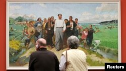 FILE - Gallery visitors view 'Chairman Mao inspects the Guangdong Countryside' by Chinese artist Chen Yanning at the 'Mahjong' exhibition of Contemporary Chinese Art at the Kunsthalle museum in Hamburg, Germany.