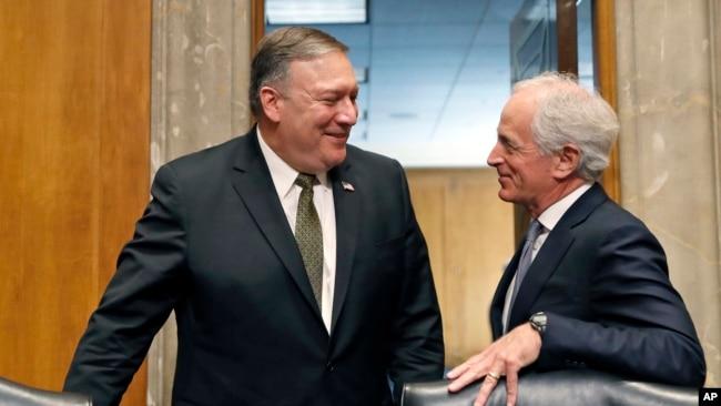 El nominado para secretario de Estado Mike Pompeo, (izquierda) conversa con Bob Corker, republicano por Tennessee, presidente de la Comisión de Relaciones Exteriores del Seando, durante una audiencia de confirmación el 12 de abril, de 2018.
