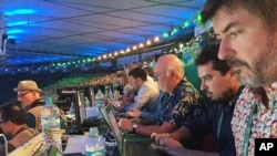 In this Aug. 5, 2016 photo, Associated Press writers John Leicester, right, and Mauricio Savarese, second from right, work at the press table in the Maracana Stadium during the opening ceremony of the Summer Olympics in Rio de Janeiro, Brazil.