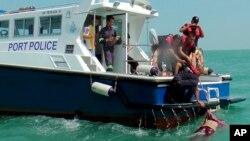 말레이시아에서 18일 여객선 침몰 사고가 발생해 5명이 숨지고 30여명이 실종된 가운데, 해양경찰이 사망자 시신을 인양하고 있다.