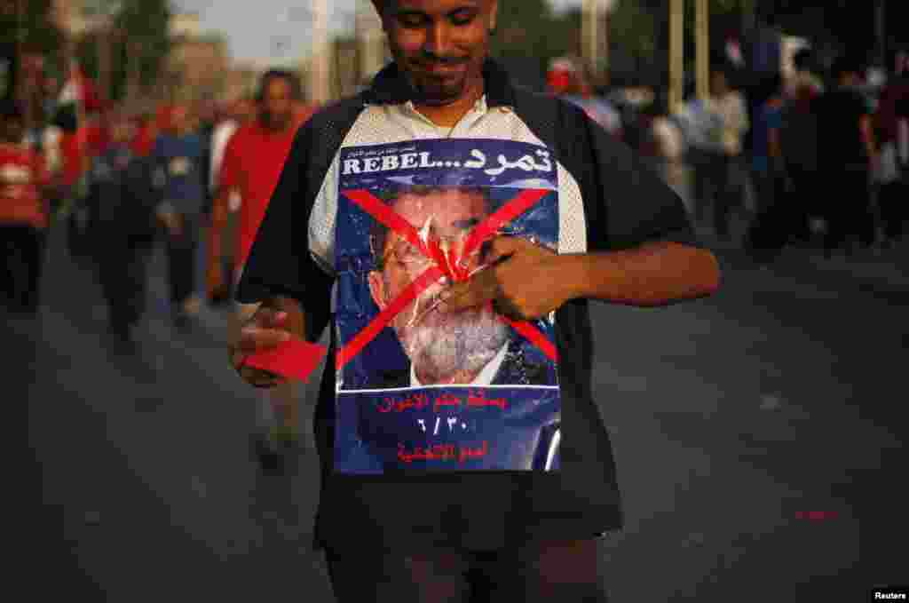 A protester opposing Egyptian President Mohamed Morsi holds a poster during a protest in front of the presidential palace in Cairo, June 30, 2013.