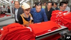 In this file photo taken on Aug. 30, 2017, Prime Minister Hun Sen, center, leans over a garment worker during a visit to a factory outside of Phnom Penh, Cambodia.