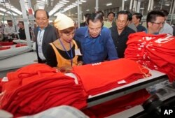 In this file photo taken on Aug. 30, 2017,Prime Minister Hun Sen, center, leans over a garment worker during a visit to a factory outside of Phnom Penh, Cambodia.