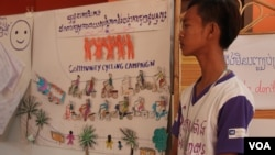 """A member of the Community Youth Network stand near his artwork to raise awareness on safe migration at the annual reflection workshop on """"Result and Role of CYN in Raising Awareness on Safe Migration and Prevention of Human Trafficking in Cambodia"""" on June 12, 2015, Phnom Penh. (Nov Povleakhena/VOA Khmer)"""