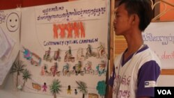"A member of the Community Youth Network stand near his artwork to raise awareness on safe migration​ at the annual reflection workshop on ""Result and Role of CYN in Raising Awareness on Safe Migration and Prevention of Human Trafficking in Cambodia"" on June 12, 2015, Phnom Penh. (Nov Povleakhena/VOA Khmer)"