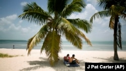 FILE - In this July 1, 2015 file photo, Marvin Hernandez, right, and Kelly Vera sit in the shade of a palm tree, in Key Biscayne, Florida.