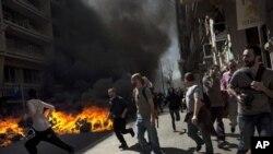 Para demonstran berlari dalam bentrokan dengan polisi di Barcelona (29/3).