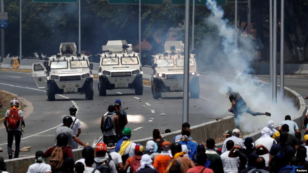 """Người biểu tình đối lập đối mặt với xe thiết giáp của quân đội gần căn cứ không quân Đại Nguyên soái Francisco de Miranda Airbase """"La Carlota"""" ở Caracas, Venezuela, ngày 30 tháng 4, 2019."""