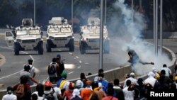 "Opposition demonstrators face military vehicles near the Generalisimo Francisco de Miranda Airbase ""La Carlota"" in Caracas, Venezuela April 30, 2019. (REUTERS/Carlos Garcia Rawlins)"