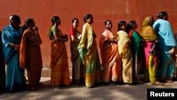 بھارت میں خواتین ایک پولنگ اسٹیشن کے باہر قطار میں اپنی باری کا انتظار کر رہی ہیں۔ فائل فوٹو