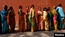 FILE - Women line up to cast their votes outside a polling station during the seventh phase of India's general election at Howrah district in the eastern Indian state of West Bengal, April 30, 2014.