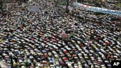 """Protesters conduct Friday Prayers in Tahrir square in Cairo. Thousands of Egyptians converged on Cairo's Tahrir square on Friday in what organizers called a """"second revolution"""" to push for deeper reforms and a speedy trial for ousted President Hosni Mubar"""