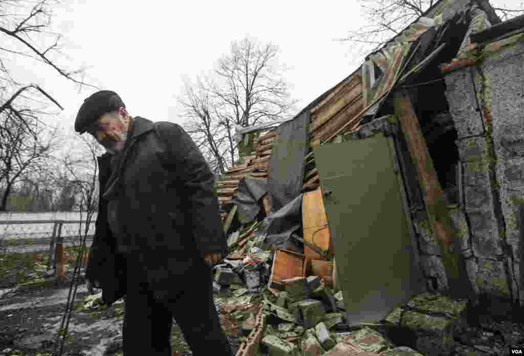 A man walks past a house damaged by recent shelling in Yenakieve, northeast of Donetsk, Feb. 2, 2015.