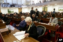 "FILE - Rep. Julia Craven Howard, R-Davie, foreground, and other North Carolina lawmakers gather for a special session regarding the ""bathroom bill,"" March 23, 2016."