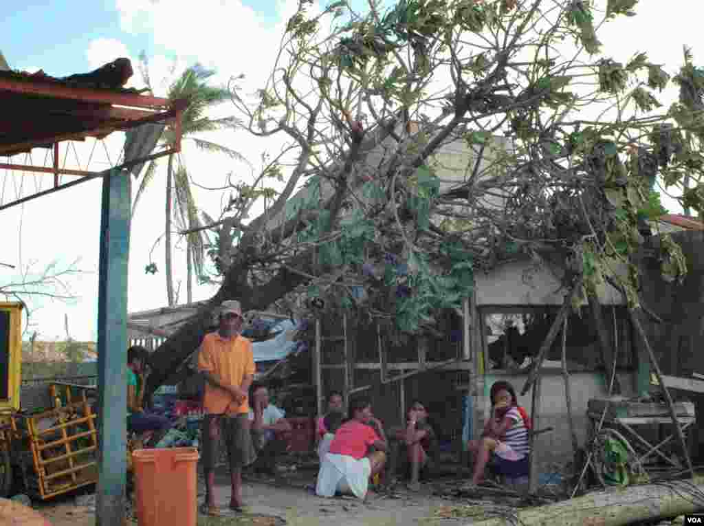 A family in front of their damaged home, Cebu, Philippines, Nov. 15, 2013. (Steve Herman/VOA)