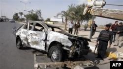 Lực lượng an ninh chuẩn bị di dời chiếc xe bị phá hủy sau vụ nổ bom gần trụ sở Bộ Nội vụ ở Baghdad, Iraq, Chủ Nhật, 19/2/2012