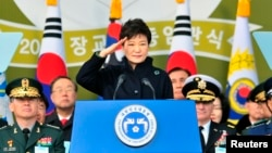 South Korean President Park Geun-hye salutes during a joint commissioning ceremony for 5,860 new officers from the Army, Navy, Air Force and Marines at the military headquarters in Gyeryong, south of Seoul, March 6, 2014.