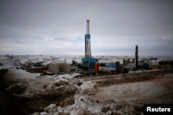 FILE - An oil derrick is seen at a fracking site for extracting oil outside of Williston, North Dakota, on March 11, 2013.