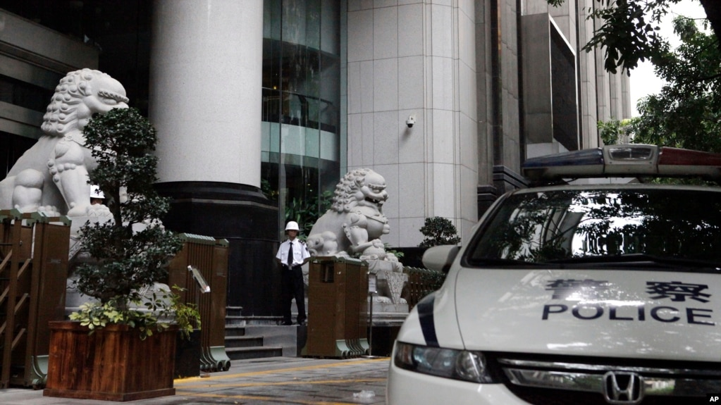 FILE - A security guard and police vehicle are seen outside the Guangzhou Intermediate People's Court in China's southern Guangdong province, May 7, 2015.