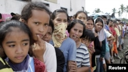 Typhoon evacuees queue for relief goods outside a local government town center in New Bataan, Compostela Valley in southern Philippines, December 6, 2012.