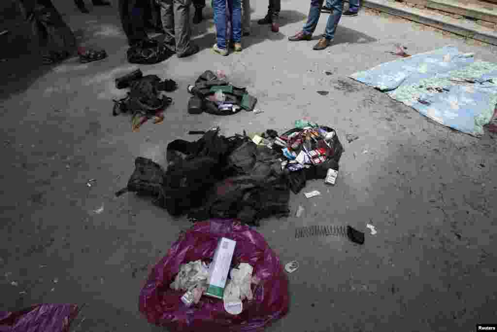 People stand near belongings of separatists killed in a fight with pro-Ukrainian forces outside a morgue in Donetsk, Ukraine, May 27, 2014.
