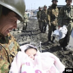 Tentara Jepang menggendong seorang bayi yang diselamatkan dari rumah keluarganya di Ishimaki City, Miyagi (14/3).