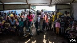 At 8 am the health post operated by Medical Teams International at Kuluba collection point is jam-packed with South Sudanese refugees waiting to undergo their first health screening. (N. Jidovanu/VOA)