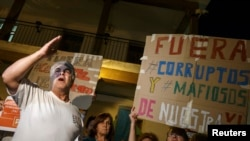 A man shouts slogans against corruption during a protest outside Madrid.