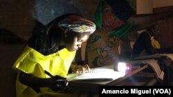 Funcionária de mesa de votos confere os dados usando uma lanterna. Wimby, Cabo Delgado, Moçambique 15 de Outubro 2019