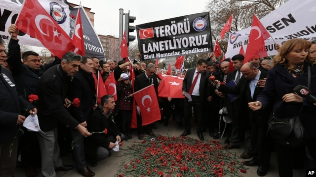 "Turkish civil servants hold a banner that reads ""We condemn terrorism"" as they lay carnations at the site of Wednesday's explosion that killed 28 people in Ankara, Feb. 20, 2016."
