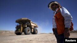 FILE - A worker checks Chile's Esperanza open pit copper mine as a truck travels along a road near Calama town, about 1,650 km (1,025 miles) north of Santiago, March 30, 2011.