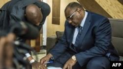 L'opposant congolais Jean-Pierre Bemba (D) examine les papiers pour s'inscrire aux élections présidentielles du 23 décembre prochain, au bureau de la Commission électorale indépendante, à Kinshasa, le 2 août 2018.