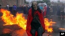 Un manifestante enmascarado protesta delante de una barricada en Tegucigalpa, la capital de Honduras.