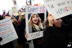 Madison Gray, a Temple University student, holds up her sign during a protest against President Donald Trump's executive order banning travel to the U.S. by citizens of Iraq, Syria, Iran, Sudan, Libya, Somalia or Yemen, Sunday, Jan. 29, 2017, at Philadelphia International Airport in Philadelphia.