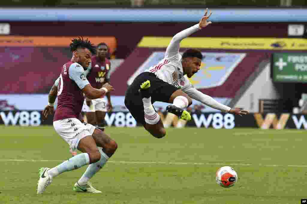 កីឡាករMbwana Samatta (ស្ដាំ) នៃក្លឹបបាល់ទាត់Sheffield United ត្រូវបានផ្ដួលដោយកីឡាករTyrone Mings របស់ក្លឹបAston Villa ក្នុងការប្រកួតបាល់ទាត់លីកកំពូលអង់គ្លេសEnglish Premier League រវាងក្រុមទាំងពីរ នៅកីឡដ្ឋានVilla Park ក្នុងទីក្រុង Birmingham ប្រទេសអង់គ្លេស កាលពីថ្ងៃទី១៧ មិថុនា ២០២០។