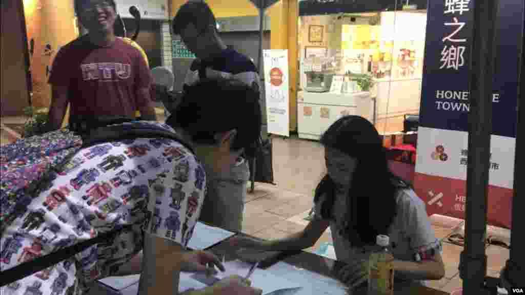 一个支持者在西门的街道旁的台湾奥运正名公投连署摊位上签名。(萧洵摄影)