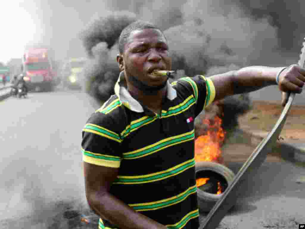A protester walks past burning tires during a rally against fuel subsidy removal in Lagos on January 3, 2012. (Reuters)
