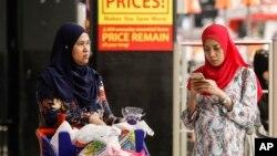 FILE - A Malaysian Muslim woman checks her mobile phone while shopping at a mall outside Kuala Lumpur, Malaysia, Aug. 18, 2015.
