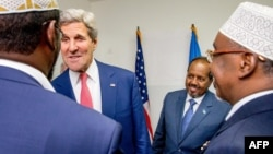 U.S. Secretary of State John Kerry, in red tie, meets with Somalia's President Hassan Sheikh Mohammed, in blue tie, and Somali regional leaders at the Mogadishu airport, May 5, 2015.