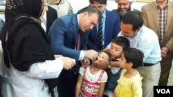والی ولایت فاریاب حین انداختن قطرات واکسین در دهن اطفال
