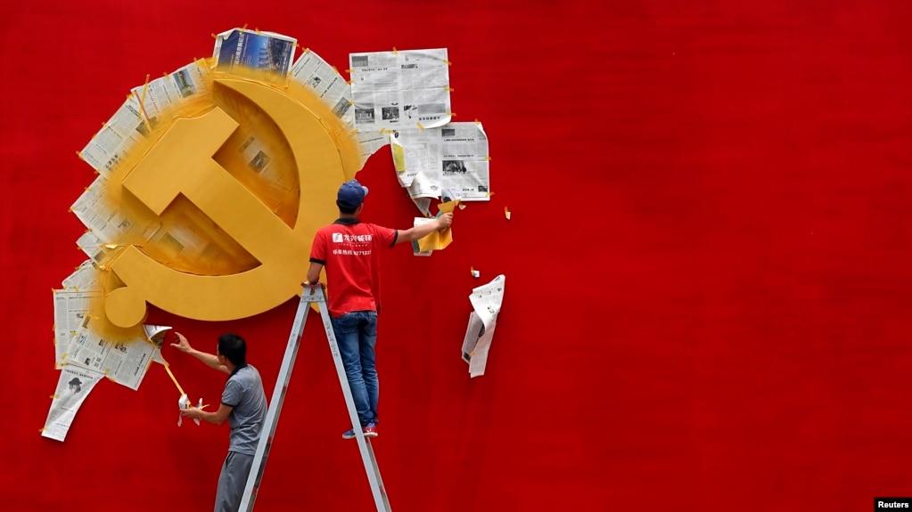 资料照:浙江省嘉兴南湖革命纪念馆的两名工人在墙上漆一面中共党旗。